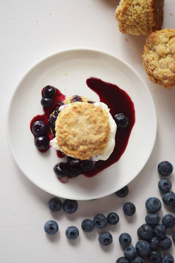 Overhead photo of blueberry shortcake on a white plate with fresh blueberries