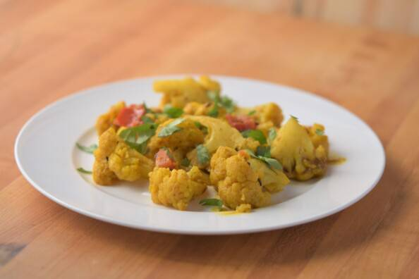 Cauliflower cooked in curry spices on a white plate