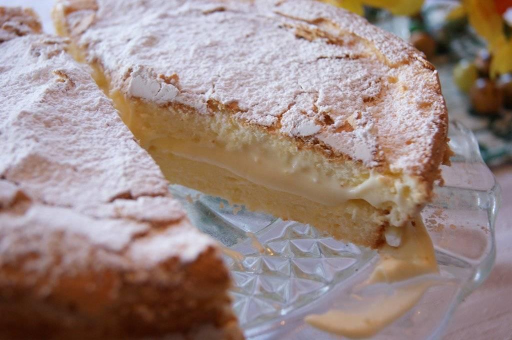 close up of gluten-free lemon sponge cake with lemon filling on a glass cake stand