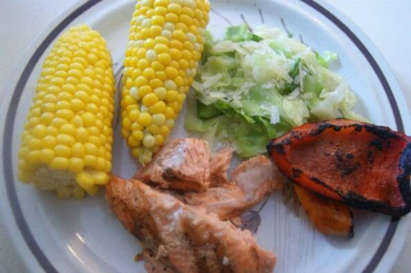 simple west coast summer meal on a plate of grilled salmon, grilled peppers, corn, and my Mother's summer cabbage recipe