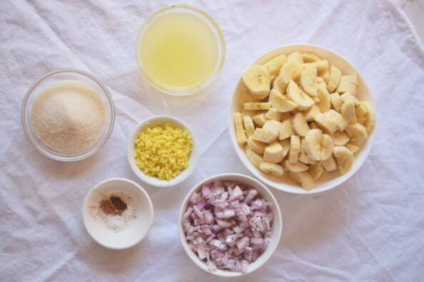 prepared ingredients for banana chutney arranged in white bowls
