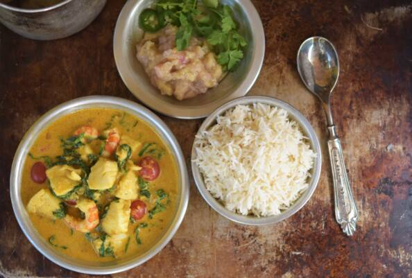 seafood curry, rice, chutney in silver bowls