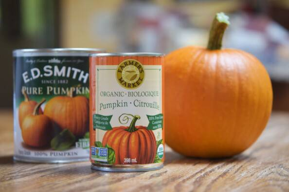 two cans of pumpkin puree and a sugar pumpkin on a wooden table