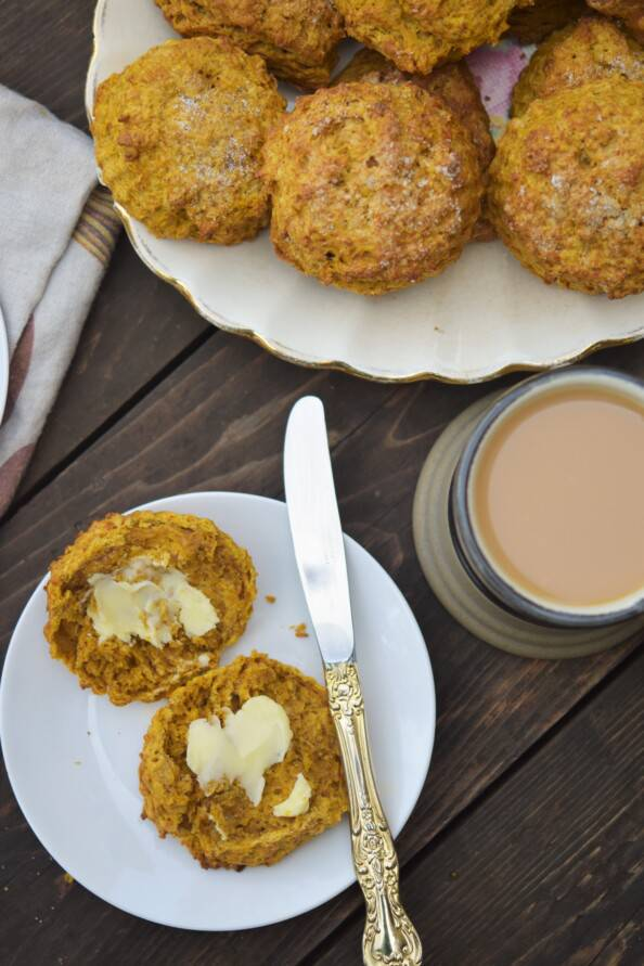 overhead shot of a buttered pumpkin scone on a white plate with a cup of tea and platter of scones