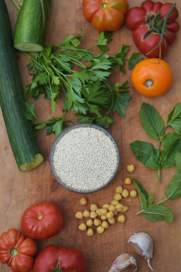overhead shot of tabbouleh ingredients on a wooden cutting board