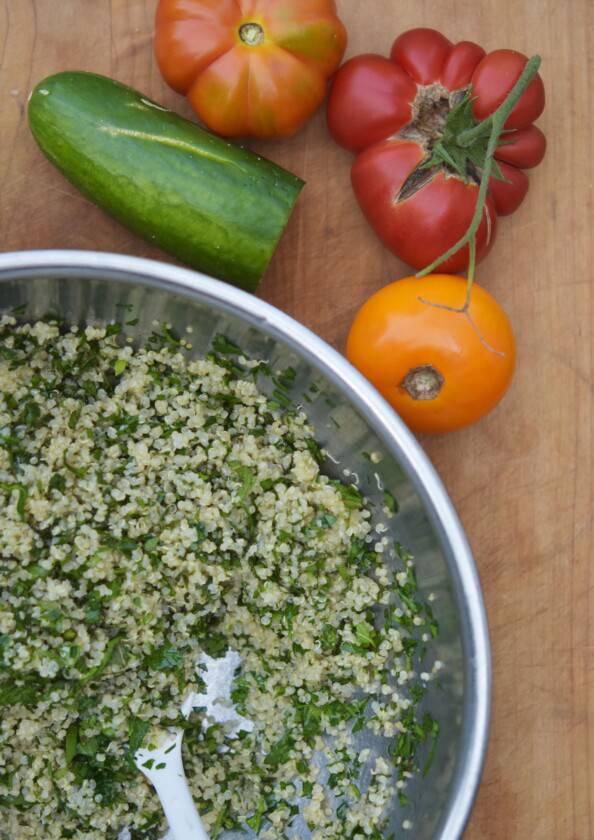 overhead photo of a metal bowl with quinoa and herbs with tomatoes and cucumbers beside it