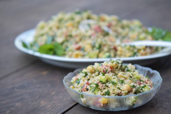 a bowl of tabbouli salad on a wooden table with a serving platter behind