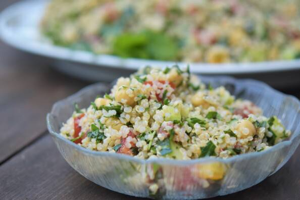 A serving of quinoa tabbouleh salad in a clear glass bowl, with a larger platter of it in the background