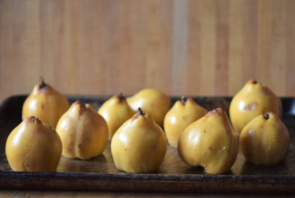 cooked whole quince on a baking sheet